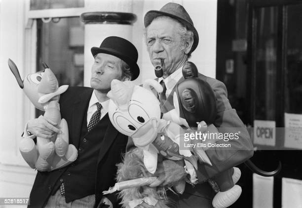 British actors Sid James and Kenneth Williams during the filming of 'Carry On At Your Convenience' 1971 They are holding inflatable toys during a...