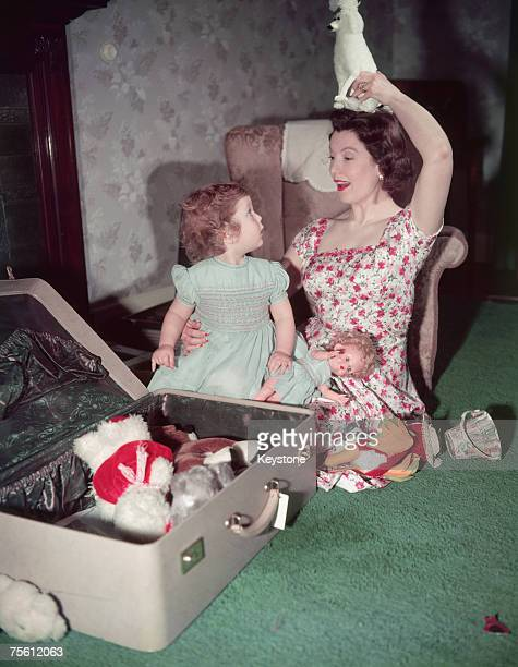 British actress and BBC continuity announcer Sylvia Peters playing with a little girl circa 1955