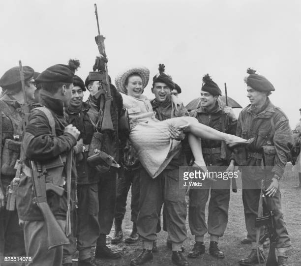 British actress and singer Elizabeth Larner is carried over the mud at Epsom Downs by a soldier of the Territorial Army before announcing the start...