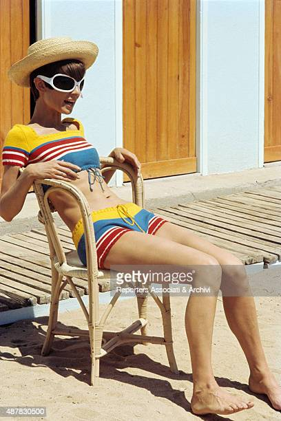 British actress Audrey Hepburn in a bath suit hat and sunglasses sitting on a beach on the set of Two For the Road 1967