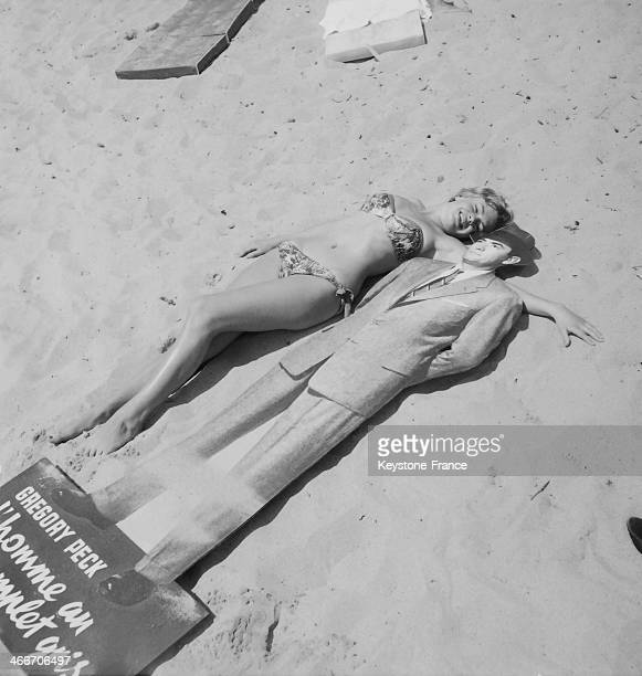 British actress Diana Dors lying on the beach with the effigie of her favourite actor Gregory Peck on May 10 1956 in Cannes France