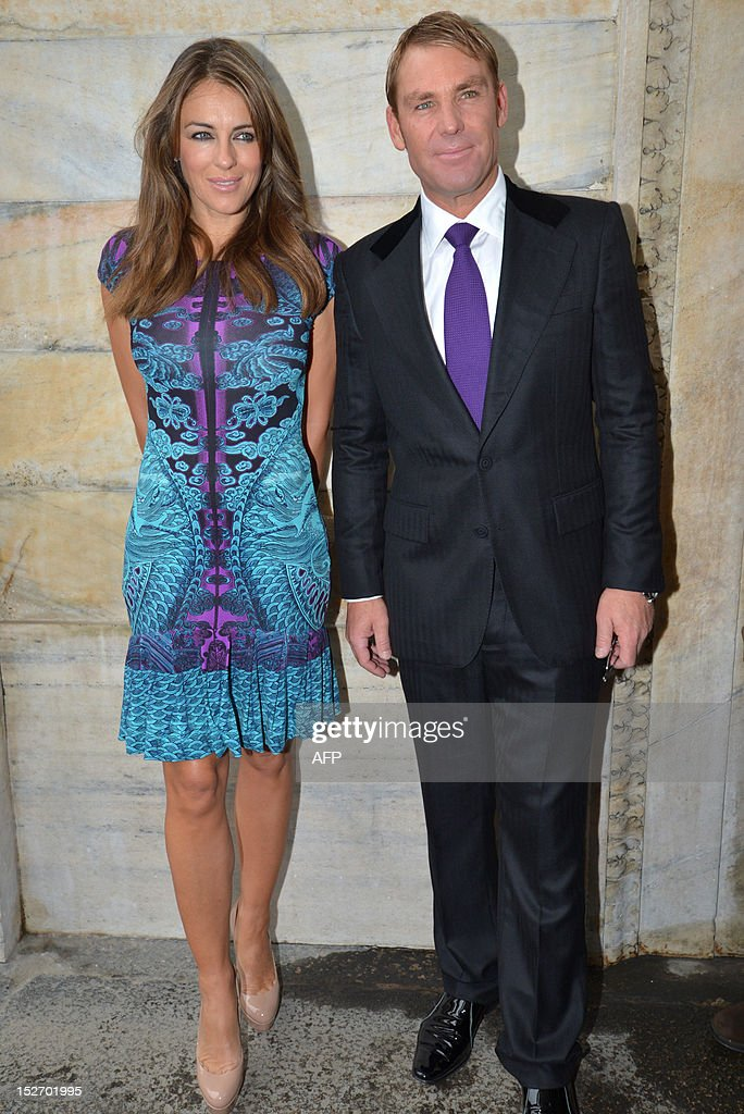 British actress Elizabeth Hurley (L) and her fiance former Australian cricketer Shane Warne pose upon arrival for the Roberto Cavalli Spring-Summer 2013 collection on September 24, 2012 during the Women's fashion week in Milan.