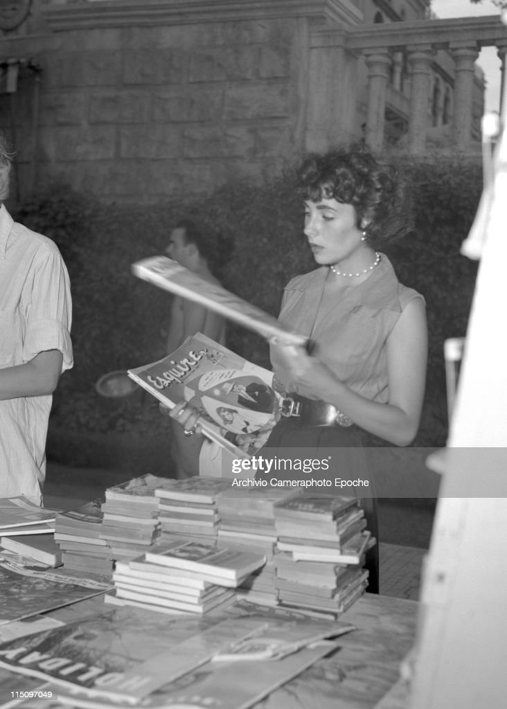 British actress Elizabeth Taylor wearing a sleeveless shirt and wide trousers chosing some magazine from a newsagent desk next to the Excelsior Hotel...