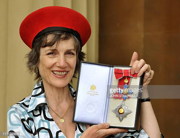British actress Harriet Walter poses for photographs with her Dame of the British Empire after receiving it from Britain's Prince Charles at...