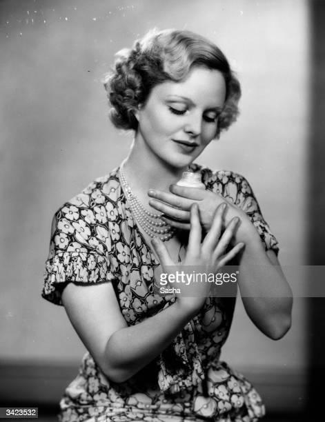 British actress Joan Barry applies skin cream to her hands