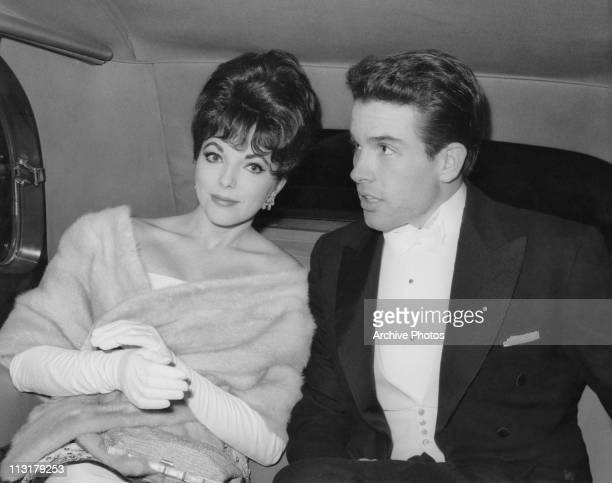 British actress Joan Collins wearing a fur wrap with American actor Warren Beatty in the back of a limousine circa 1961