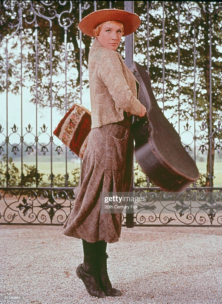 British actress Julie Andrews stands on her toes while she holds a guitar case in a scene from the film 'The Sound of Music,' directed by Robert Wise, 1965.