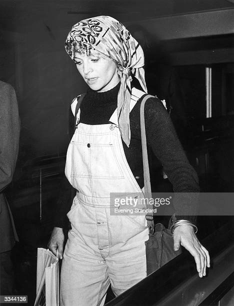 British actress Julie Christie arrives at Heathrow Airport wearing a pair of dungarees and a headscarf October 1973