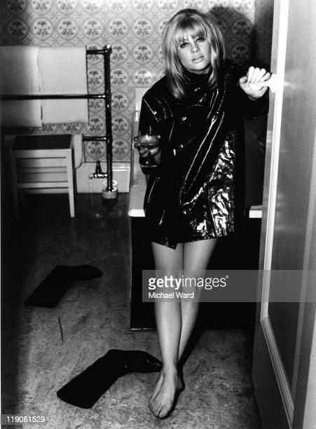 British actress Julie Christie barefoot wearing a black PVC jacket 1963