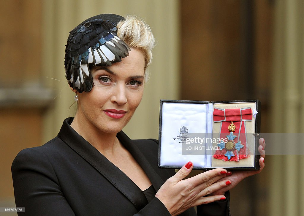 British actress Kate Winslet holds her neck badge after being made a Commander of the Order of the British Empire (CBE) for services to drama by Britain's Queen Elizabeth II at an investiture ceremony at Buckingham Palace in central London on November 21, 2012.