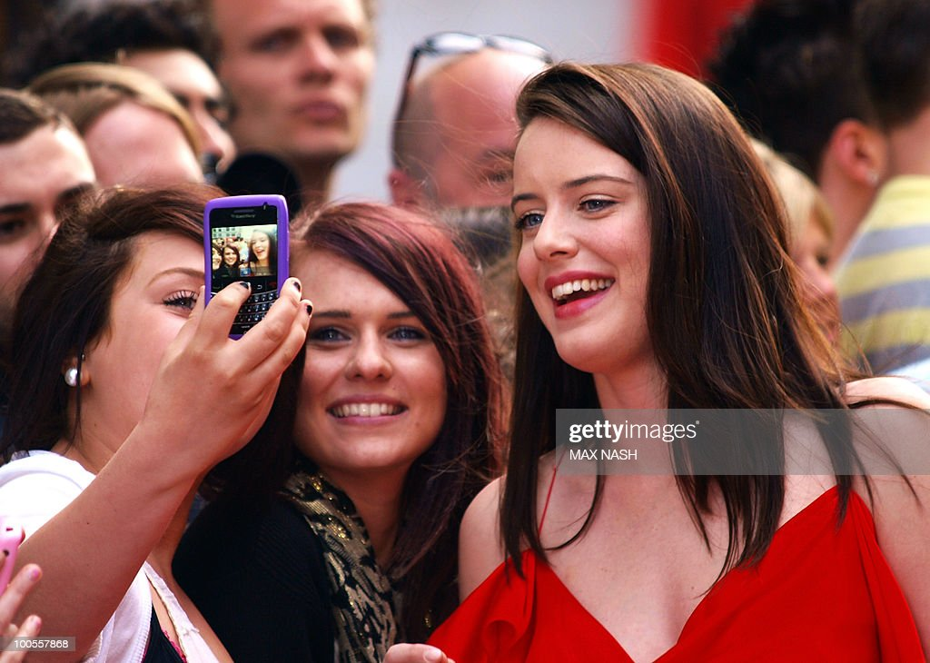 British actress Michelle Ryan poses with her fans as she arrives at the World Premiere of her latest film, '4.3.2.1' in London's Leicester Square on May 25, 2010. AFP Photo/MAX