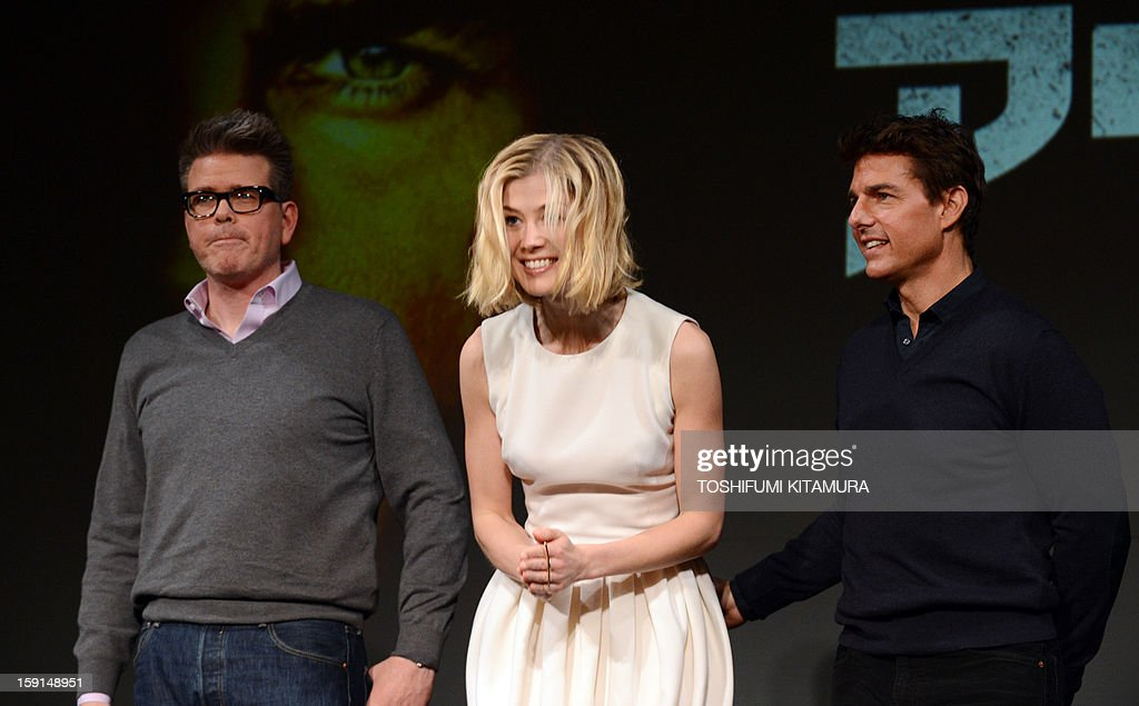 British actress Rosamund Pike (C) bows as US actor Tom Cruise (R) and director Christopher McQuarrie (L) look on during a photo session at a press conference for their latest movie, 'Jack Reacher' in Tokyo on January 9, 2013. The movie's Japan premier will be held laon January 9 and will be shown nation wide from Feburary 1.