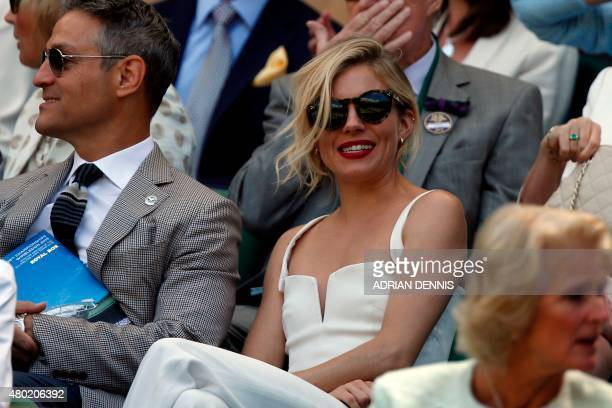 British actress Sienna Miller sits on Center Court during the men's singles semifinal match between Serbia's Novak Djokovic and France's Richard...