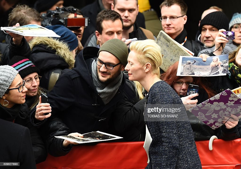 British actress Tilda Swinton (R) poses for a photo while signing autographs upon arrival for the photo call for the film 'Hail, Cesar' screened as opening film of the 66th Berlinale Film Festival in Berlin on February 11, 2016. The 66th Berlin film festival starts on February 11, 2016 with a spotlight on Europe's refugee crisis. / AFP / TOBIAS SCHWARZ
