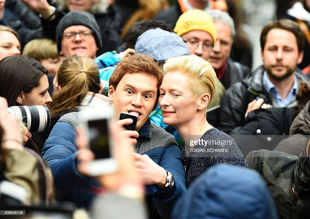 British actress Tilda Swinton poses for a photo while signing autographs upon arrival for the photo call for the film 'Hail, Cesar' screened as opening film of the 66th Berlinale Film Festival in Berlin on February 11, 2016. The 66th Berlin film festival starts on February 11, 2016 with a spotlight on Europe's refugee crisis. / AFP / TOBIAS SCHWARZ