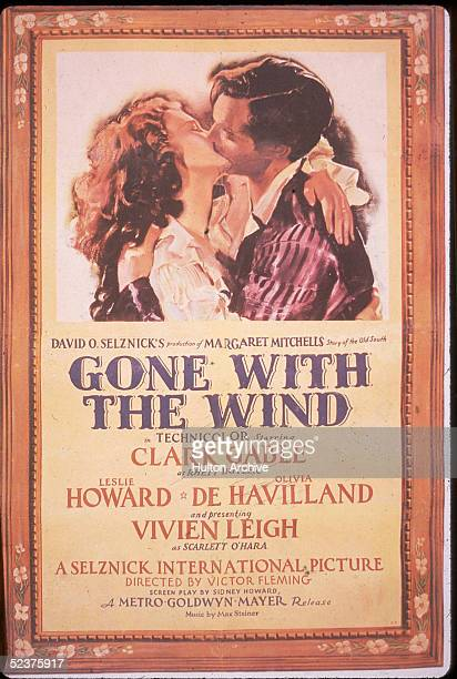 British actress Vivien Leigh as Scarlett O'Hara kisses American actor Clark Gable as Rhett Butler in this promotional poster for the movie 'Gone With...
