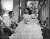 British actress Vivien Leigh with dress designer Walter Plunkett during a break from filming the American civil war epic 'Gone With the Wind'