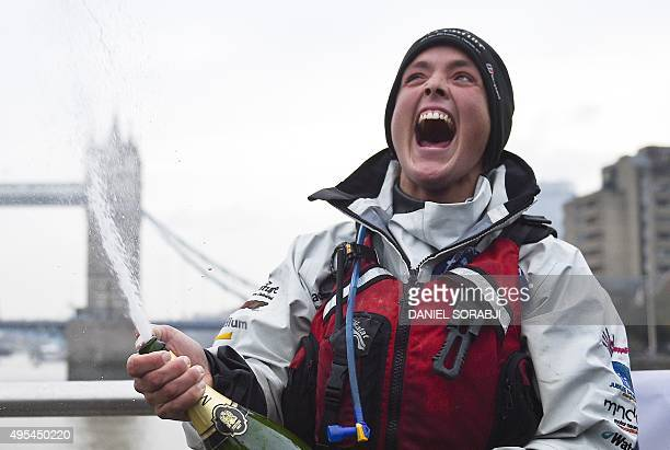 British adventurer Sarah Outen sprays a bottle of champagne on the River Thames in London on November 3 as she celebrates completing her fourandahalf...