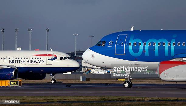 A British Airways aircraft passes a BMI passenger jet on the tarmac at Heathrow airport in London UK on Thursday Dec 22 2011 British Airways parent...