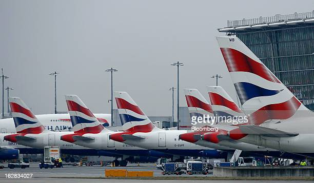 British Airways aircraft stand at departure gates at Terminal 5 at Heathrow Airport in London UK on Thursday Feb 28 2013 British Airways parent...