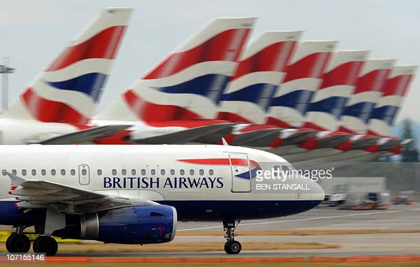 A British Airways aircraft taxis past other parked British Airways aircraft at Terminal 5 of Heathrow Airport in west London on July 30 2010 British...