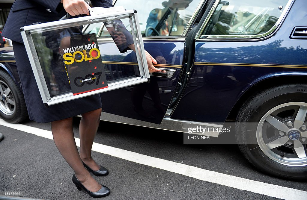 British Airways ambassador Helena Flynn holds British author William Boyd's new James Bond novel 'Solo' as she enters a Jensen car during a photo call a day ahead of the book's publishing in central London on September 25, 2013. Solo follows British agent 007 on an African adventure. AFP PHOTO/Leon Neal