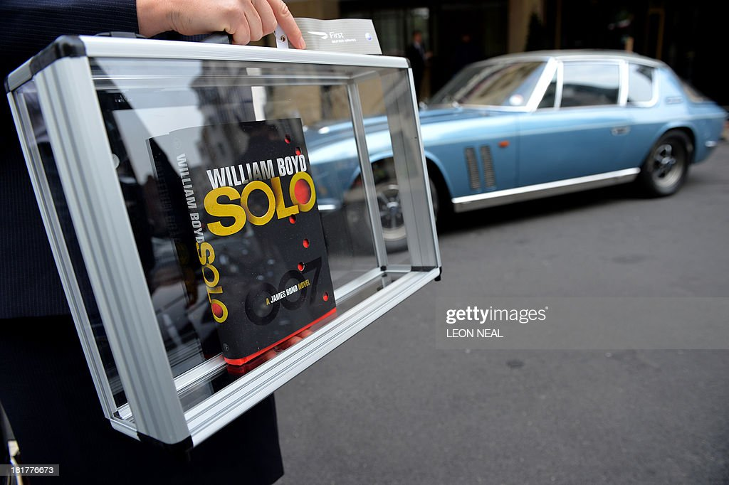 British Airways ambassador Helena Flynn holds British author William Boyd's new James Bond novel 'Solo' during a photo call a day ahead of the book's publishing in central London on September 25, 2013. Solo follows British agent 007 on an African adventure. AFP PHOTO/Leon Neal