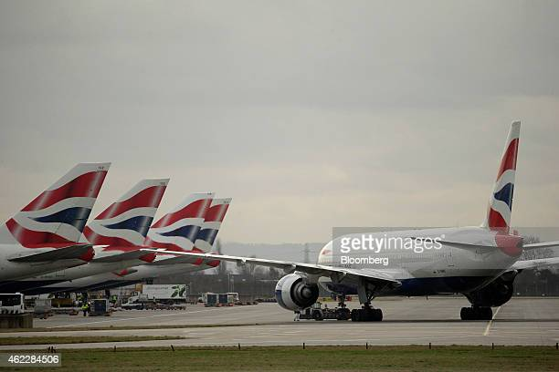 British Airways logos sit on the tailfins of passenger aircraft operated by International Consolidated Airlines Group SA at London Heathrow airport...