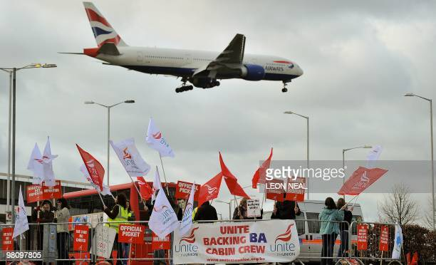 A British Airways plane flies over striking British Airways cabin crew members at Heathrow Airport on the second day of a fourday strike on March 28...