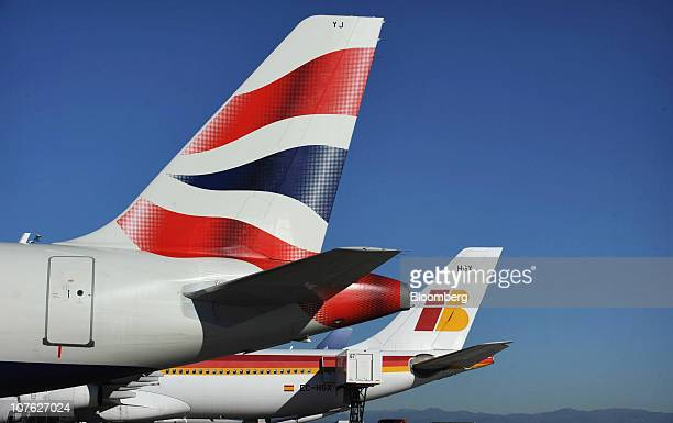 British Airways Plc left and Iberia Lineas Aereas de Espana SA logos are seen on aircraft tailfins at Barajas airport in Madrid Spain on Thursday Dec...