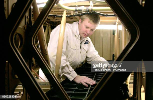 British Airways's engineer Marc Morley working inside the wing of one of the airline's Concordes places in position a section of the new kevlar and...