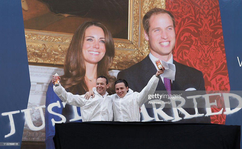 British Ambassador to Germany Simon McDonald (L) and graffiti artist Oliver Kray smile after they spray 'Just Married' below a giant poster of the the Royal Highnesses Prince William, Duke of Cambridge and Catherine, Duchess of Cambridge at the British embassy on April 29, 2011 in Berlin, Germany. The wedding of Britain's Prince William and his fiancee Kate Middleton will be celebrated at Westminster Abbey in London on April 29, 2011.
