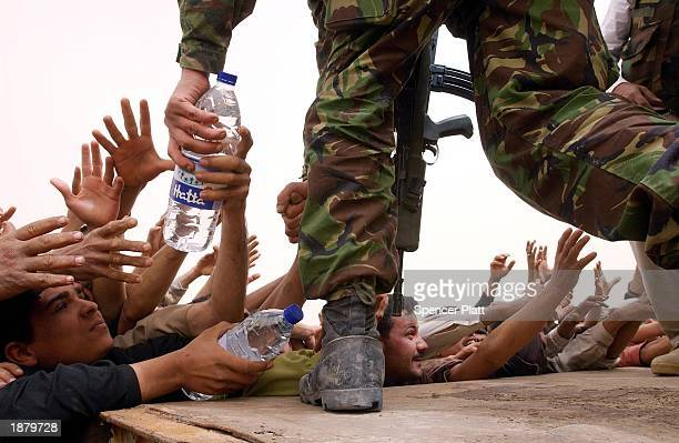 British and American soldiers hand out water to thousands of Iraqi citizens March 27 2003 in the Iraqi city of Al Zubaya south of Iraq's second...