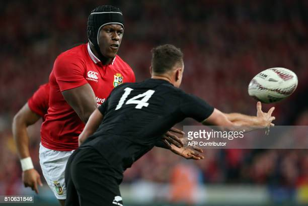 British and Irish Lions lock Maro Itoje passes the ball in front of New Zealand's right wing Israel Dagg during the third rugby union Test match...
