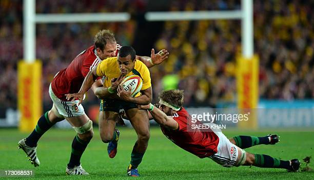British and Irish Lions players Geoff Parling and Alun Wyn Jones tackle Australia's Will Genia during the third and final rugby union Test in Sydney...