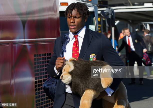British and Irish Lions rugby player Maro Itoje carries the lion mascot as he boards a coach upon the team's arrival at the airport in Auckland on...