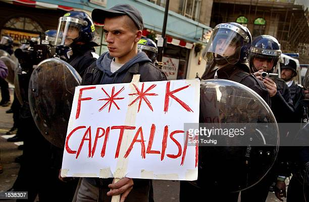 British anticapitalist protester carries a banner in front of riot police at a May Day demonstration May 1 2002 in London There were sporadic clashes...