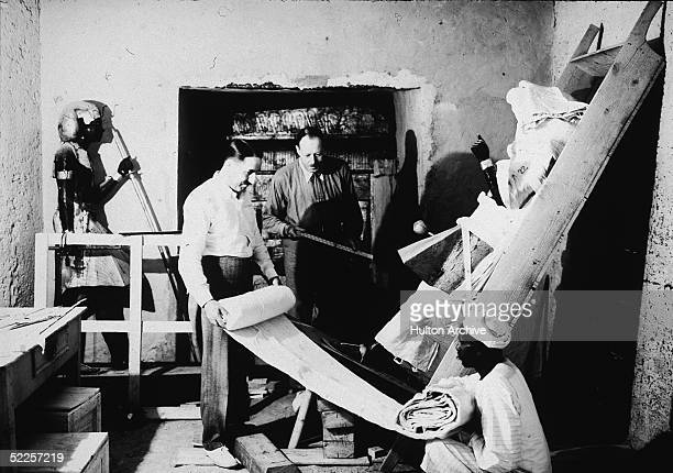 British archaeologists Howard Carter and Arthur Callender carry out the systematic removal of objects from the antechamber of the tomb of Pharaoh...