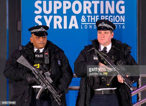 British armed police officers stand guard outside the QEII centre in central London on February 4 ahead of the start of a donor conference entitled...