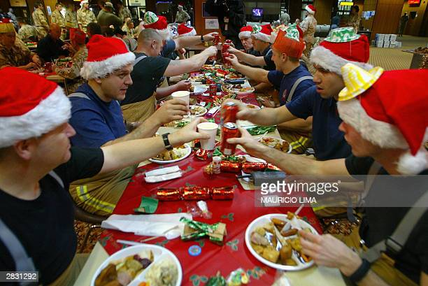 British army firefighters wearing Santa Claus hats cheer during a Christmas lunch in MultiNational Division headquarters at Basra International...