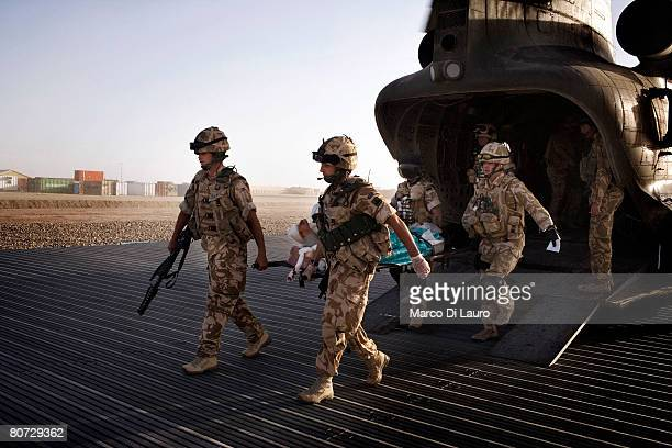 British Army Medical Emergency Response team from the UK Med Group carries injured Afghan National Army Sgt Quem Abdulh out of the helicopter on June...