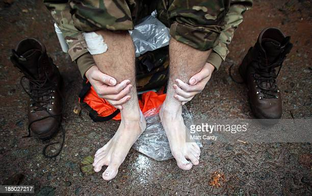 British Army officer cadet from the Royal Military Academy Sandhurst attends to his feet as he takes a break before begining a command task at a...