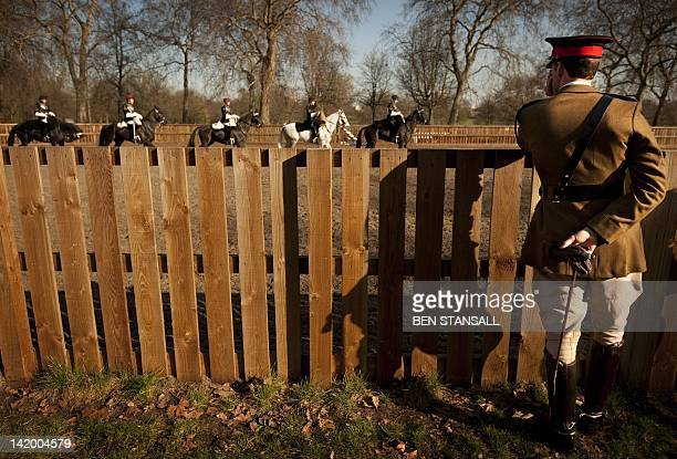 A British Army officer watches members of the Household Cavalry riding in an outdoor riding school as they prepares for the Major General's...