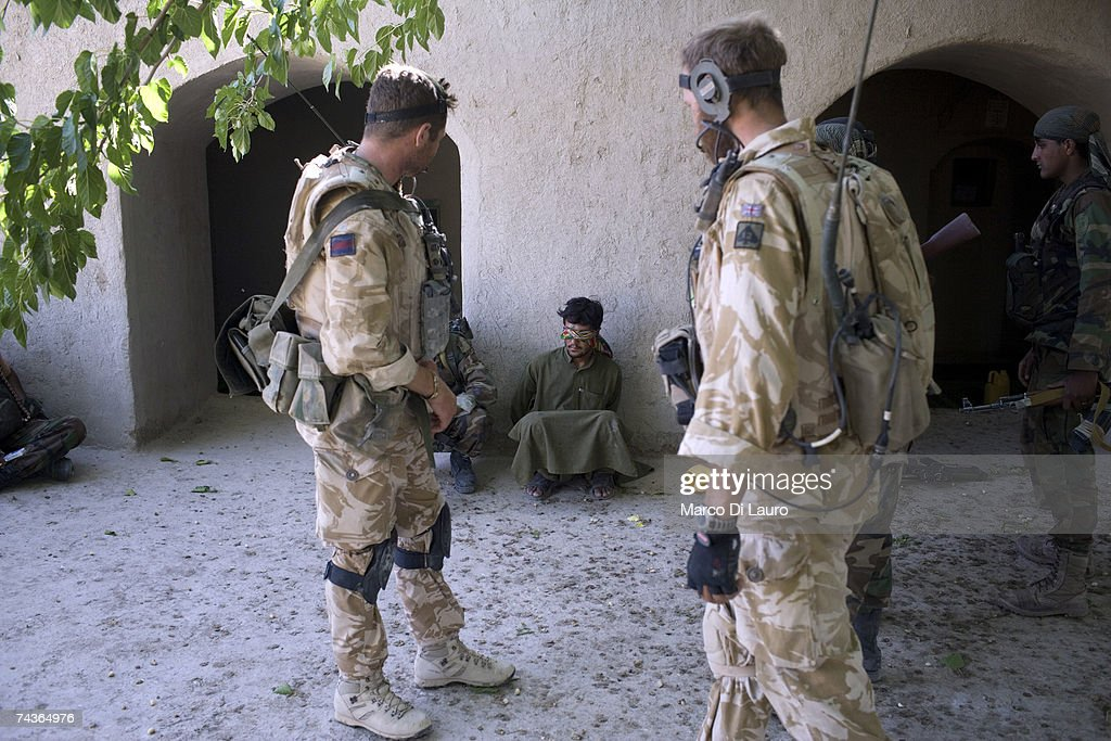 British Army Officers, Captain Alex Corbet Burcher from the 1st Battalion Welsh Guards Regiment, and Captain Edward Janvrin from the 2nd Battalion of the Royal Gurkha Rifles look at a blind folded allegedly suspected Taliban, later released because innocent, arrested by ANA ( Afghan National Army) Soldiers during 'Lastay Kulang' Operation on May 30, 2007 in Sangin Valley, Helmand Province, Afghanistan. The two British Officer had nothing to do with the arrest of this person and with the way ANA soldiers decided to blind fold him. British troops from The Inkerman Company, 1st Battalion Grenadier Guards, part of ISAF Task Force Helmand, are mentoring the Afghan National Army while conducting security operations on behalf of the Government of Afghanistan in Helmand Province.