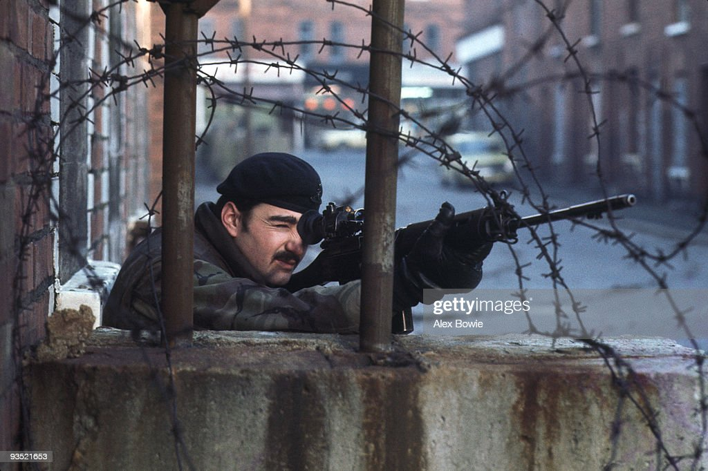 A British Army sniper takes cover behind a makeshift peace line dividing Catholic and Protestant communities in north Belfast, 20th February 1978.