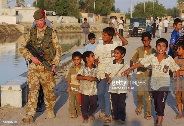 British Army soldier from the 1st Black Watch Regiment walks with children behind during a patrol on September 26 2004 in the village of Al Musharrah...