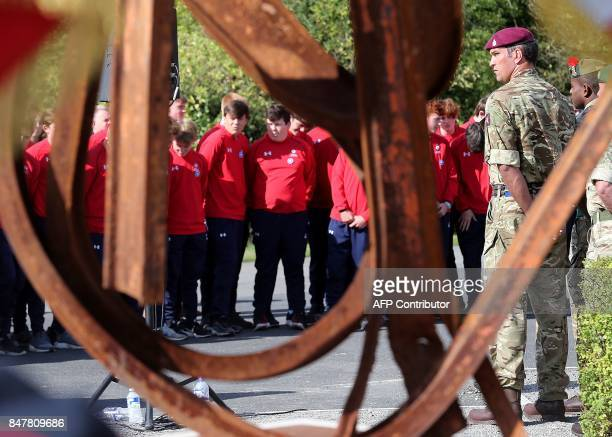 British army soldiers and young rugby players look on during the inauguration of a monument created by French former rugby player JeanPierre Rives...