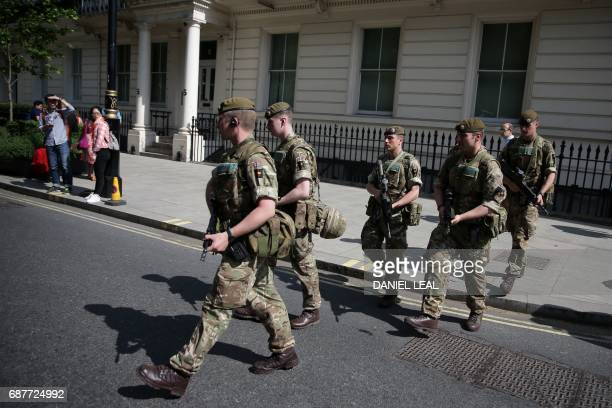 TOPSHOT British Army soldiers are led by a police officer into Buckingham Palace in central London on May 24 2017 Britain deployed soldiers to key...
