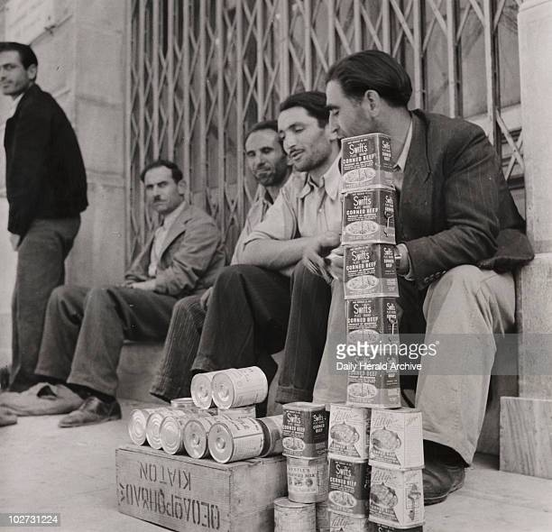 British Army supplies of corned beef being sold in Greece 18 June 1946 'Corned beef staked high for sale Sellers sitting behind their goods waiting...