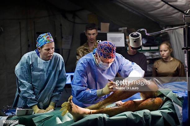 British Army surgeon Major Andy Bruce takes out fragments from the legs of injured British Army soldier Simon Peacock from the Royal Anglion Regiment...